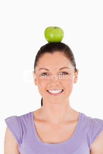Portrait of an attractive woman holding an apple on her head while standing