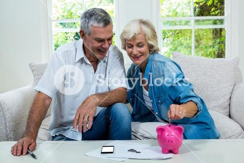 Senior woman putting coins in piggy bank while sitting with man on sofa