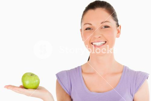 Attractive woman holding an apple while standing