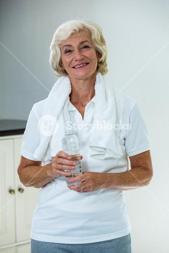 Portrait of active senior woman standing with water bottle