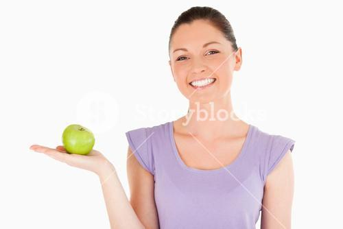 Beautiful woman holding an apple while standing