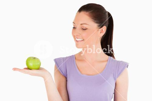 Good looking woman holding an apple while standing