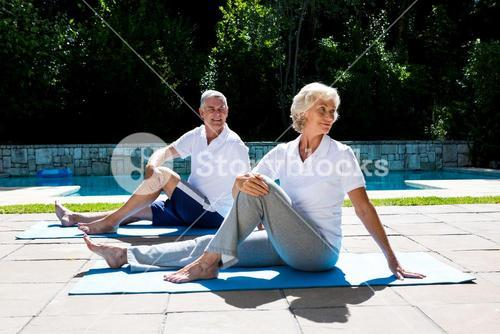 Senior couple exercising on mat at poolside