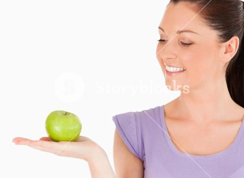 Charming woman holding an apple while standing