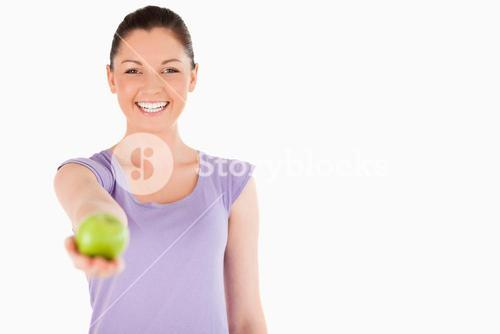 Gorgeous woman holding an apple while standing