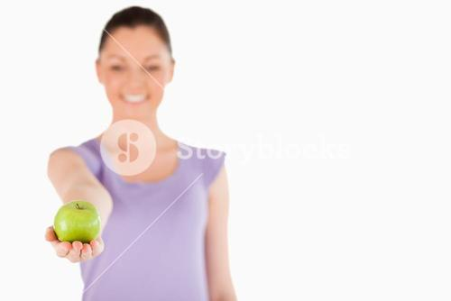 Pretty woman holding an apple while standing