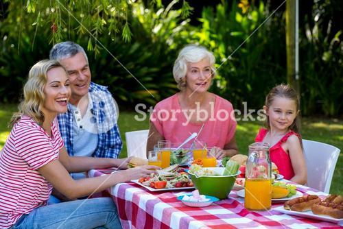 Happy family having meal in yard