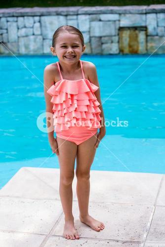 Girl standing by swimming pool