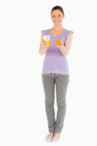 Young beautiful woman holding an orange and a glass of orange juice