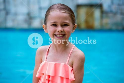 Portrait of girl standing by swimming pool