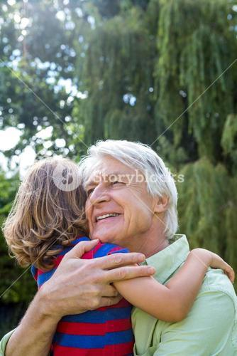 Happy grandfather hugging grandson at yard
