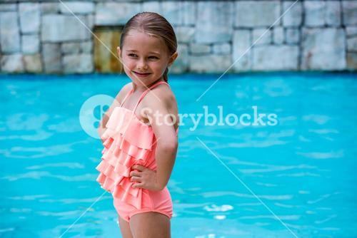 Girl standing at poolside