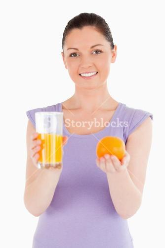 Portrait of an attractive woman holding an orange and a glass of orange juice while standing