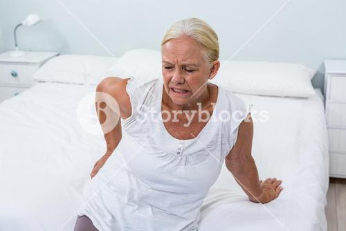 Senior woman suffering from back pain at home