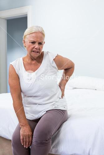 Senior woman suffering from back pain while sitting in bedroom