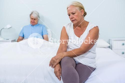Sad senior couple sitting in bedroom