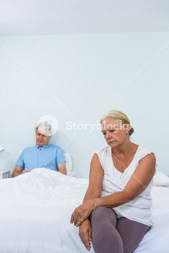 Sad senior couple sitting on bed