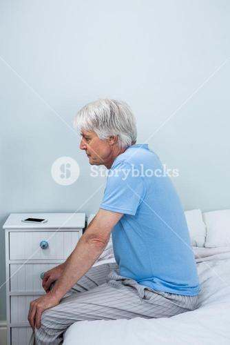 Side view of thoughtful senior man sitting on bed