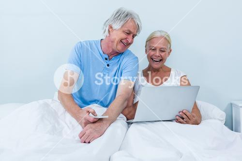 Happy retired couple using laptop while sitting on bed
