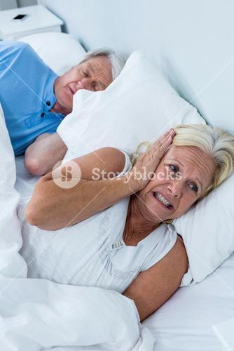 Senior woman covering ears while man snoring