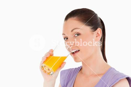 Attractive woman drinking a glass of orange juice while standing