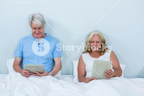 Happy retired couple using digital tablets