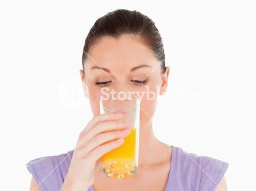 Good looking woman drinking a glass of orange juice while standing