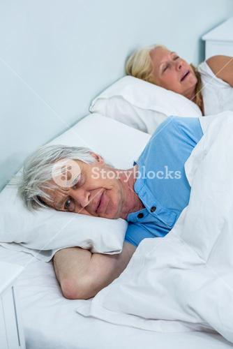 Thoughtful senior man relaxing on bed while woman snoring