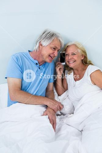 Happy retired couple listening to music through smartphone