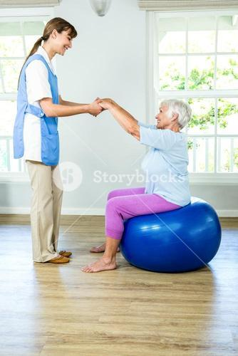 Smilnig nurse assisting senior woman
