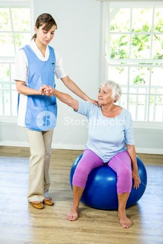 Senior woman exercising with nurse
