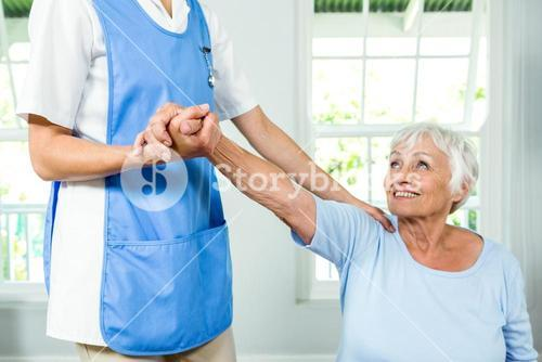 Smiling senior woman exercising with nurse