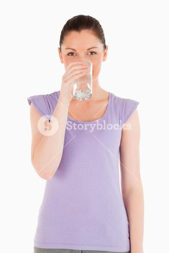 Charming woman drinking a glass of water while standing