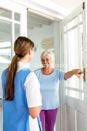 Smiling senior woman standing with nurse by door