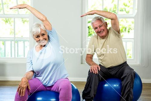 Portrait of smiling senior man and woman exercising