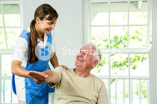 Smiling nurse assisting aged man