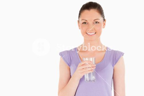 Beautiful woman holding a glass of water while standing