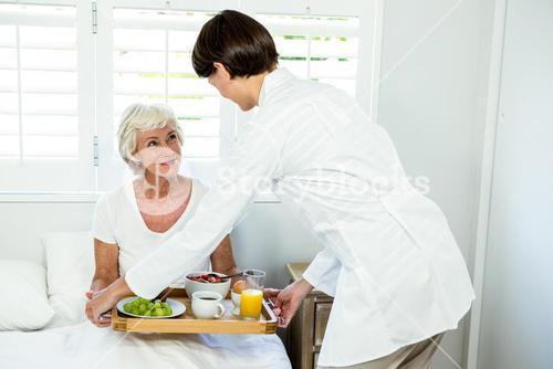 Female caregiver serving breakfast to senior woman