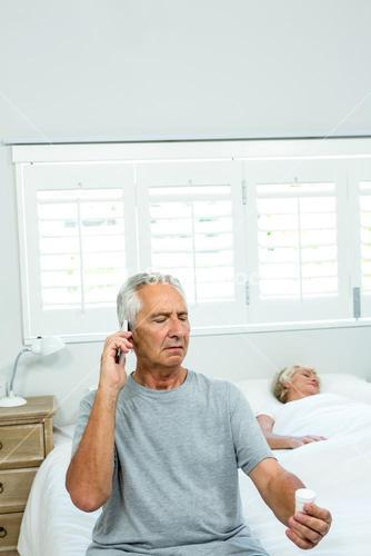 Old man talking on phone with woman sleeping