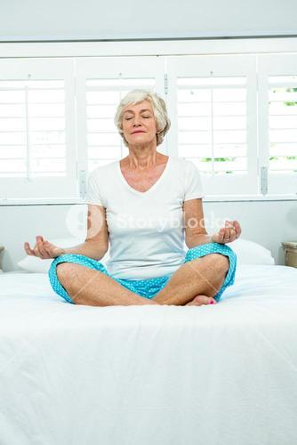 Aged woman doing yoga on bed