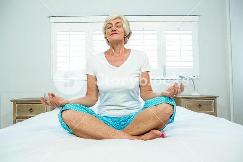 Old woman performing yoga on bed