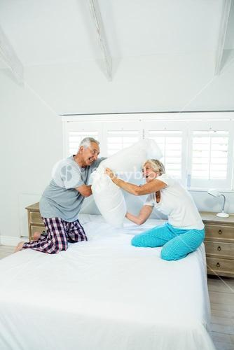 Old couple playing with pillows on bed