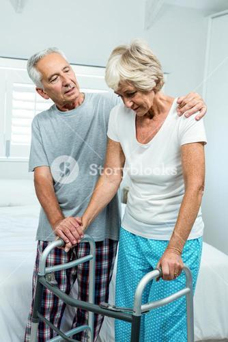 Aged woman with walker by man in bedroom
