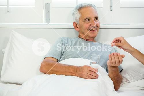 Cropped image of doctor giving medicine to senior man