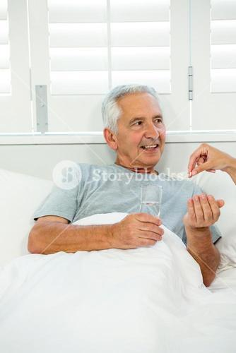 Cropped image of doctor giving medicine to old man