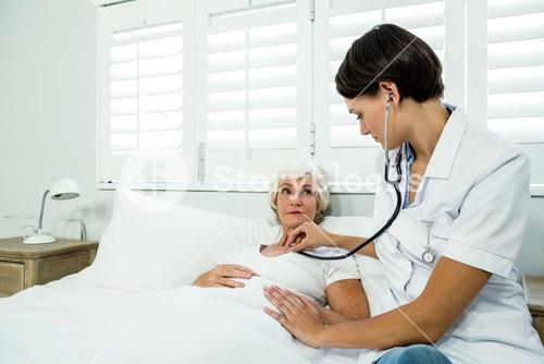 Female doctor auscultating aged woman at home