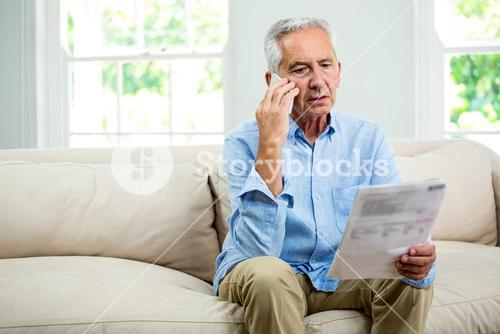 Old man talking on phone in living room at home