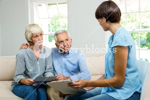Consultant talknig with senior couple at home