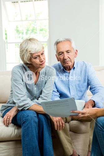 Cropped image of consultant showing report to senior couple