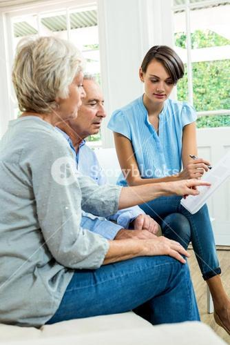 Aged couple reading report with female consultant